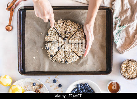 A woman is slicing the dough for spelt flour scones before they go to the oven. - Stock Photo
