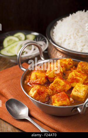 Paneer and sweet pepper curry with rice on wooden background - Stock Photo