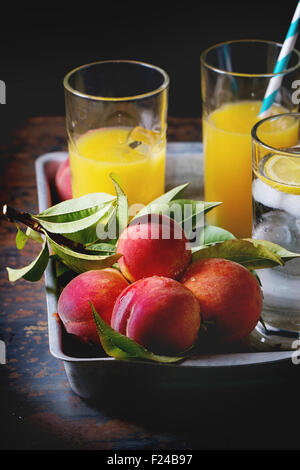 Peaches on branch with leaves and glasses with peach juice and limonade with ice cubes in aluminum tray over old - Stock Photo