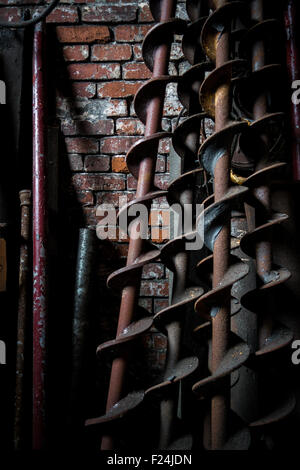Large augers or drill bits lean against a red brick wall, bathed in shadows - Stock Photo