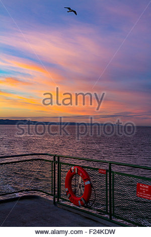Clouds catch various shades of wonderful colors after sunset as seen from a Washington State Ferry crossing from - Stock Photo