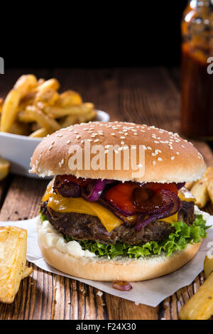 Homemade Burger with French Fries on an old wooden table - Stock Photo