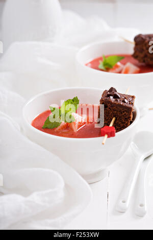 Strawberry dessert soup with a piece of chocolate cake - Stock Photo
