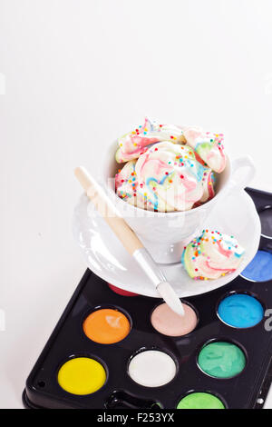 Colorful meringues painted rainbow colors with sprinkles - Stock Photo