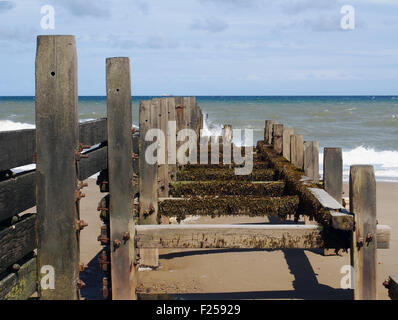 Battered wooden groyne, part of the sea defences at Walcott on the North Norfolk coast. - Stock Photo