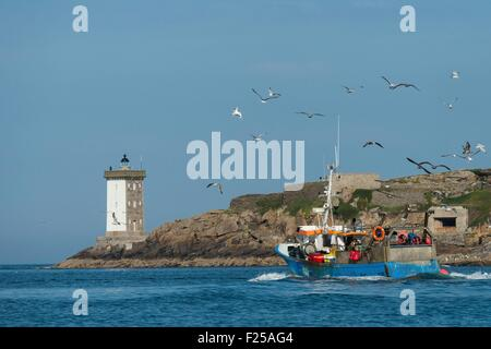 France, Finistere, Le Conquet, Fishing boat in front of the lighthouse Kermorvan - Stock Photo