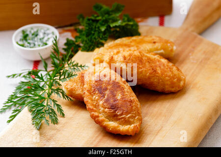 Colombian empanadas (snack sized savory patties) on wooden board. Latin cuisine - Stock Photo
