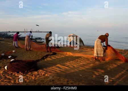 Sri Lanka, Western Province, Negombo, fishermen sorting their nets on the Porathota beach - Stock Photo