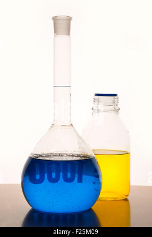 Measuring glasses on a table with blue and yellow liquid of a chemical laboratory - Stock Photo