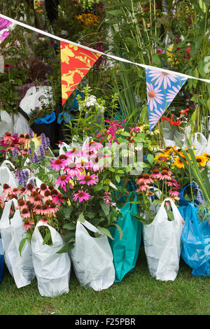 Bought flowers in plastic bags waiting to be collected at RHS Wisley flower show. Surrey, England - Stock Photo