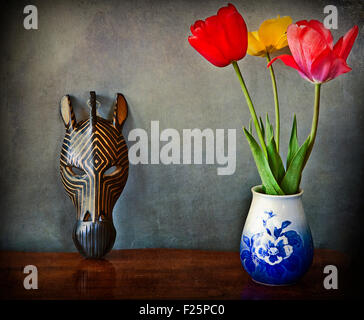 Vintage still life, three tulips in vase and wooden African mask - Stock Photo