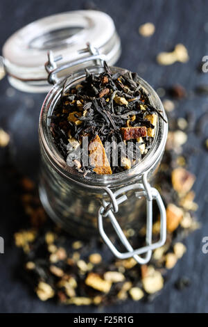 Indian black tea with orange, and spices in a glass jar. - Stock Photo