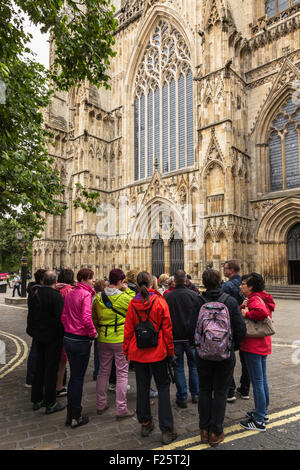 Group of Tourists Outside York Minster in Colourful Clothing - Stock Photo