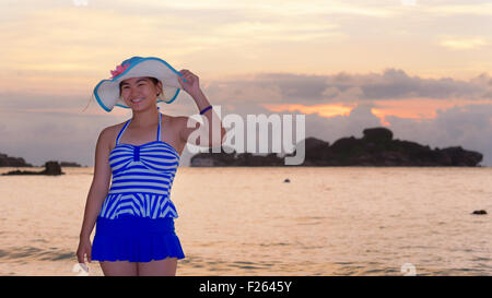 Tourist girl in a blue striped swimsuit pose with happiness on the beach and beautiful landscape of sky over the - Stock Photo