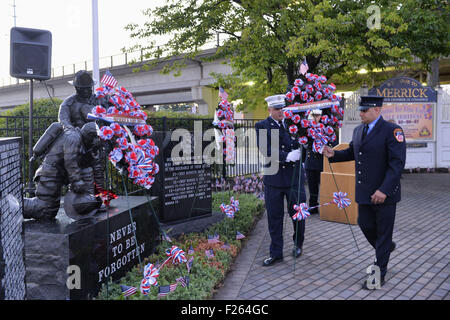 Merrick, New York, USA. 11th Sep, 2015. A Merrick and NYC firefighter place a wreath in memory of Ex-Chief Ronnie - Stock Photo