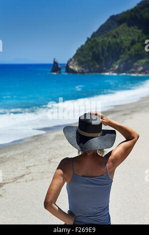 Rear view of a mature woman overlooking lonely beach on Pelion Peninsula, Thessaly, Greece - Stock Photo
