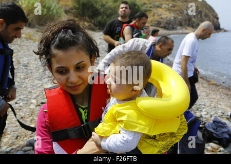 Lesbos, Greece. 09th Sep, 2015. A mother carries her child at the beach shore of Lesbos. Hundreds of refugees, mainly - Stock Photo
