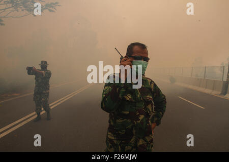 Riau, Indonesia. 12th Sep, 2015. An Indonesian soldier uses a walkie talkie to report the haze situation at Kampar - Stock Photo