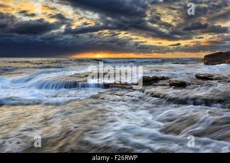 strong coastal waves on sandstone rocks near Maroubra beach of pacific coast in Sydney at sunrise - Stock Photo