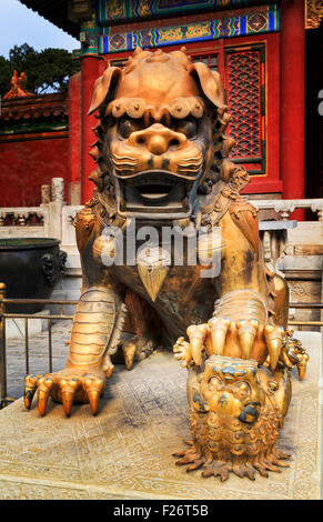 Close up frontal view of bronze gold plated imperial lion statue at Forbidden city palace in Beijing - Stock Photo
