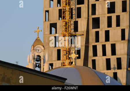 The bell and clock tower of the Resurrection of Christ Orthodox Cathedral of Tirana beside a new high rise building - Stock Photo