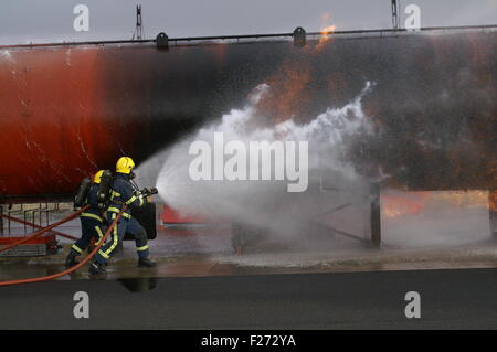 fire fighters fighting fire with hose - Stock Photo