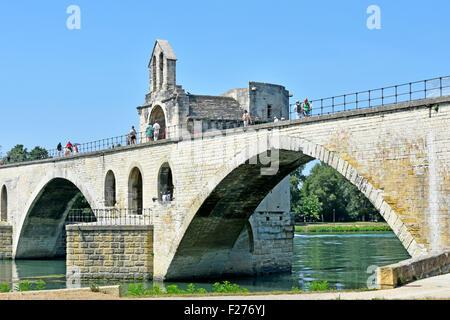 Avignon France The Pont d'Avignon bridge and tourists visiting the French St Nicholas chapel on the River Rhone - Stock Photo
