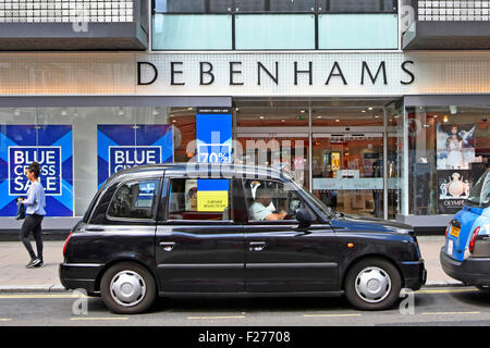 London taxi driver in London black cab in Oxford Street waiting outside entrance to Debenhams department store West - Stock Photo