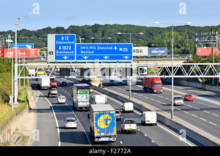M25 motorway railway bridge & container freight train crossing above road traffic at junction 28 Brentwood Essex - Stock Photo