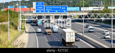 Container freight train crossing railway bridge above road traffic at junction 28 of  M25 motorway at Brentwood - Stock Photo