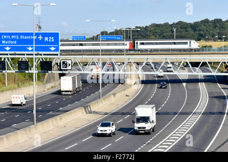 M25 motorway bridge and Greater Anglia inter city passenger train crossing above road traffic junction 28 at Brentwood - Stock Photo
