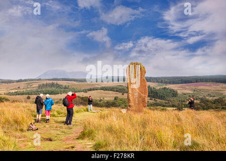 Tourists taking photos of one of the standing stones on Machrie Moor, Arran, North Ayrshire, Scotland. - Stock Photo