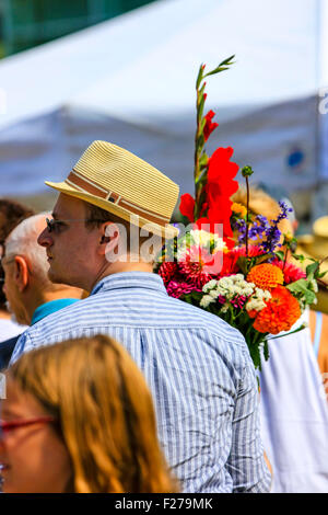 Man wearing a summer hat carries a bouquet of flowers he purchased at the Saturday Market in Madison WI - Stock Photo