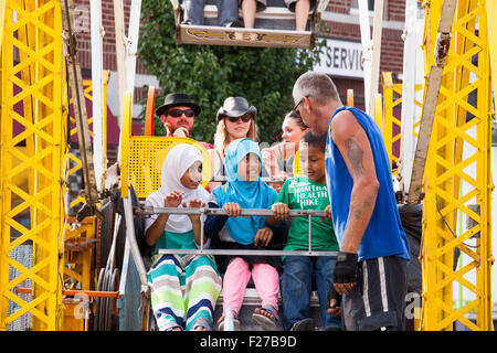 Hamtramck, Michigan - A worker fastens children into a ferris wheel during Hamtramck's Labor Day festival. - Stock Photo