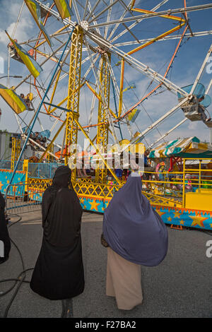 Hamtramck, Michigan - Two Muslim women watch their children on a ferris wheel during a Labor Day festival. - Stock Photo