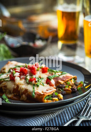 Spicy black bean and corn enchiladas with sauce and cheese - Stock Photo