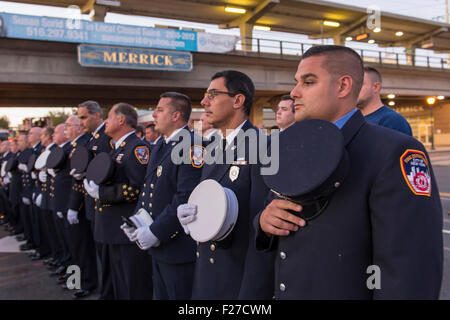 Merrick, New York, USA. 11th September 2015. Firefighters from Merrick and New York City stand in line and hold - Stock Photo