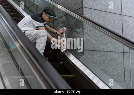 Man cleaning the glass of an escalator in Kyoto Station, Kyoto, Japan. - Stock Photo