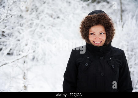 Cheerful Caucasian Young Woman in Snowy Weather in park with snow-covered trees, Copy Space - Stock Photo
