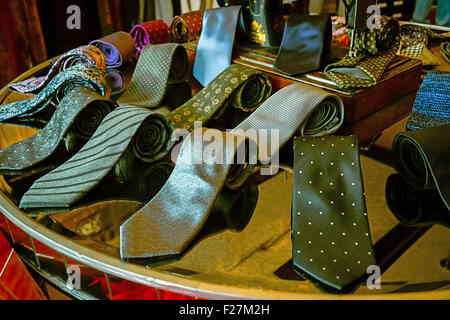 A collection of men's fine silk ties displayed on tabletop in men's clothing store - Stock Photo