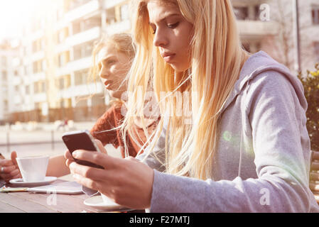 Teenage girl text messaging at sidewalk cafe, Munich, Bavaria, German - Stock Photo