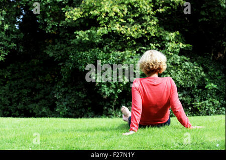 Back view of middle aged woman wearing coral pink coloured top and blue trousers sitting on grass outdoors - Stock Photo