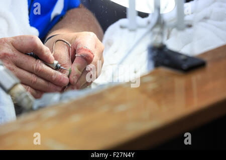 Crafting and wet drilling of a jade pendant in Hokitika, New Zealand - Stock Photo