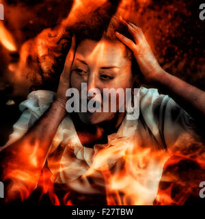 a woman looking through flames, screaming - Stock Photo
