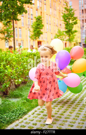 happy little girl outdoors with balloons - Stock Photo