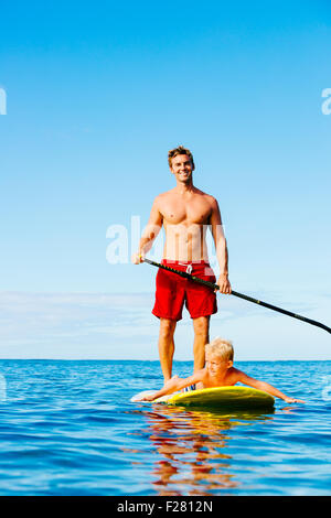 Father and Son Stand Up Paddling. Having Fun Outdoors. Summer Lifestyle.