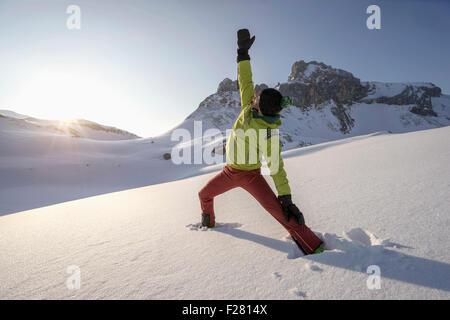 Man doing yoga on snowcapped mountain during sunrise, Tyrol, Austria - Stock Photo