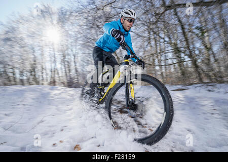 Mountain biker riding a bike in a snowy forest, Bavaria, Germany - Stock Photo