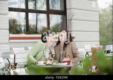 Mature women having breakfast in sidewalk cafe, Bavaria, Germany - Stock Photo