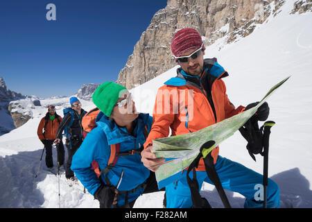 Ski mountaineers reading map while climbing on snowy mountain, Val Gardena, Trentino-Alto Adige, Italy - Stock Photo